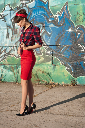 Sexy hot brunette pinup woman model wearing red headband, checked shirt and skirt, black high heels, posing, standing against green and blue grafitti background. Copy space photo