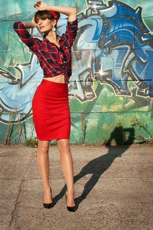 Sexy hot brunette pinup woman model wearing red headband, checked shirt and skirt, black high heels, posing, standing against green and blue grafitti background