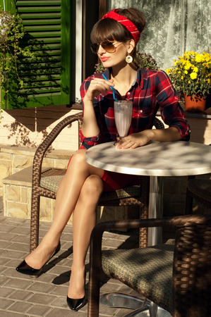Pretty brunette woman with long legs wearing red skirt, checked shirt, band, aviator sunglasses, patent leather shoes, resting in a wickered chair in a street cafe, drinking her cold milk shake cocktail. On a hot summer day photo