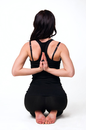 downward: Pretty young woman practicing yoga in studio, back view. Over white background, copy space