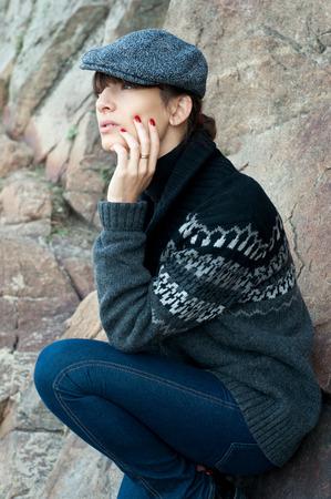 Elegant beautiful brunette woman model wearing boyish clothes like tutpleneck sweater, jacket, jeans, cap, red nails, siting near rocks. Autumn fashion