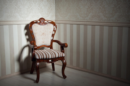 Retro wooden chair in empty room against light beige wallpapers. Copy space photo