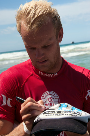 stu: MANLY AUSTRALIA - FEBRUARY 15: Stu Kennedy signing autograph on a cap for his fan after  the competition in semi final among men in the Australian Surfing Open at Manly Beach. February 15, 2015 Manly, Australia.