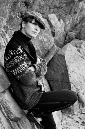 turtleneck: Black and white portrait of elegant beautiful brunette woman model wearing boyish clothes like turtleneck sweater, knitted jacket, jeans, cap, red nails, patent leather shoes, siting near rocks. Autumn fashion