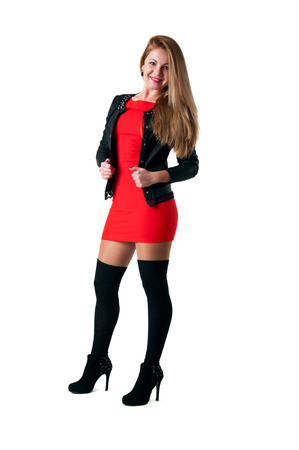 Pretty young blond woman model wearing tight short red dress, black leather jacket, black stockings, high heel shoes, standing, posing, looking at camera and smiling with toothy smile. Isolated over white background Stock Photo