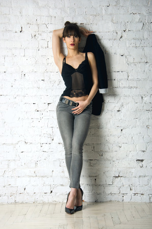 mujeres eroticas: Colorido retrato de estudio de modelo de mujer muy sexy con cuerpo increíble piernas largas hermosas de pie y vistiendo pantalones de mezclilla, top de lencería negro, posando, mirando a la cámara. De ladrillo blanco pared blanca de fondo, copia espacio