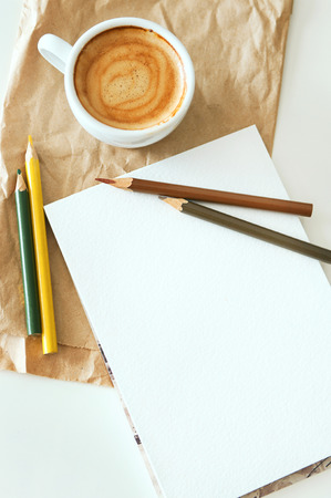 Delicious breakfast cup of strong aroma espresso coffee with color pencils and watercolor paper notepad on a recyclable brown paper and white table, copy space, vintage toning photo