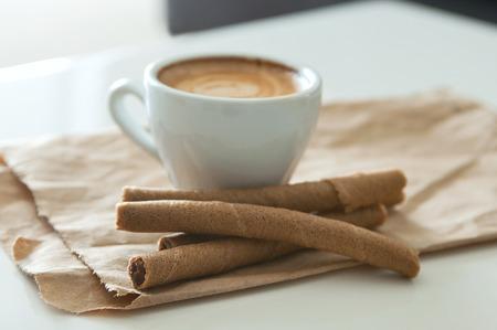 reciclable: Delicioso desayuno taza de caf� espresso fuertes tubos aroma y la oblea de chocolate en un papel marr�n reciclable. Enfoque selectivo, foco principal en un tubo de oblea frontal