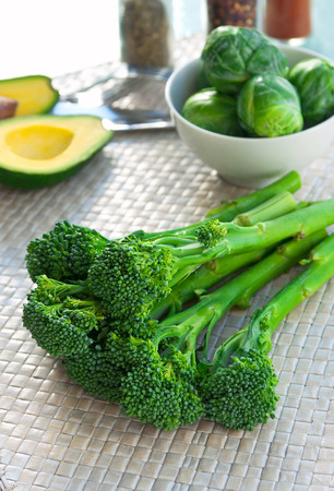brocolli: Fresh ripe juicy and delicious vegetables brocolli, brussels sprouts, bunch of asparagus, avocado cut in halves, herbs and spices on a wickered mat on a table ready to be cooked