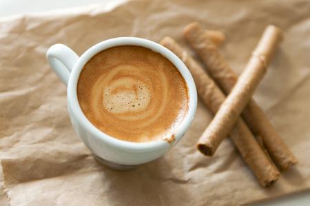 reciclable: Delicioso desayuno taza de café espresso fuertes tubos aroma y la oblea de chocolate en un papel marrón reciclable.