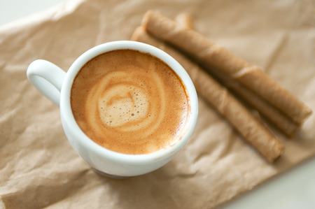 Delicious breakfast cup of strong aroma espresso coffee and chocolate wafer tubes on a recyclable brown paper.