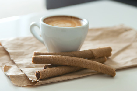 Delicious breakfast cup of strong aroma espresso coffee and chocolate wafer tubes on a recyclable brown paper. Selective focus, main focus on a front wafer tube Stock Photo