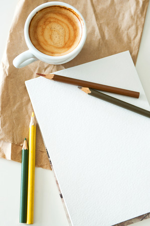 Delicious breakfast cup of strong aroma espresso coffee with color pencils and watercolor paper notepad on a recyclable brown paper and white table, copy space, vintage toning