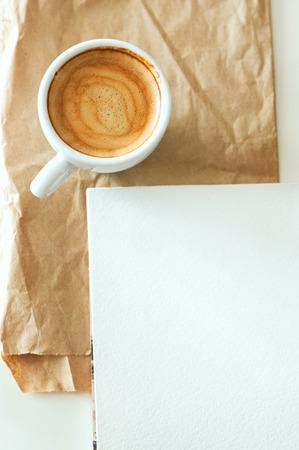 reciclable: Delicioso desayuno taza de café expreso fuerte aroma y acuarela papel bloc de notas en un papel marrón reciclable y blanco de mesa, espacio de copia, la tonificación de la vendimia