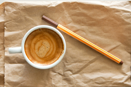 Delicious breakfast cup of strong aroma espresso coffee with brown ink pencil on a recyclable brown paper, copy space