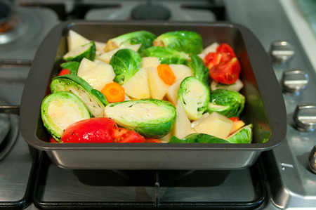 Freshly cut vegetables potatoes, tomatoes, carrot, brussels sprouts for a ragout, seasoned with salt, pepper and olive oil, in a pan to be cooked. Selective focus, main focus on brussels sprout, copy space