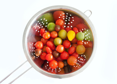 Colorful red yellow and green cherry tomatoes washed in a stainless colander, isolated on white background, copy space
