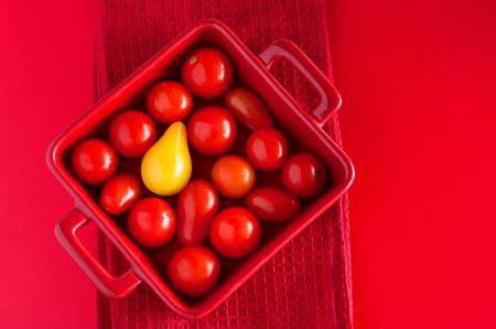 Vierkante plaat met cherry tomaten op een rode tafel met een theedoek, bovenaanzicht. Kan gebruikt worden als een illustratie van een idee van verschil, die buiten de menigte. Kopieer de ruimte Stockfoto