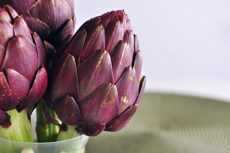 Selection of fresh organic purple artichokes on the table with green woven mat against light background, copy space, natural light