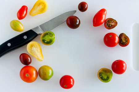 paring knife: Sharp and shiny paring knife surrounded with cherry tomatoes of different size, shape and color yellow red and green, lying on a white cutting board. Top view, copy space