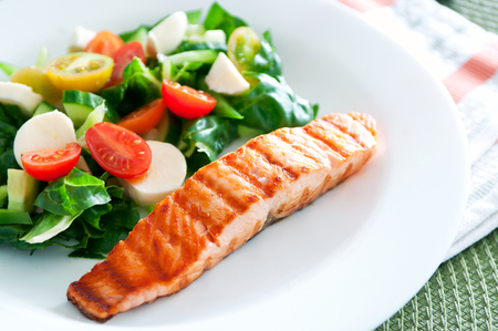 Tasty slice of fried salmon served with mix salad of kale leaves, cherry tomatoes and bocconcini cut in halves, cucumber, served on a white plate. Healthy food. Selective focus, copy space Stock Photo