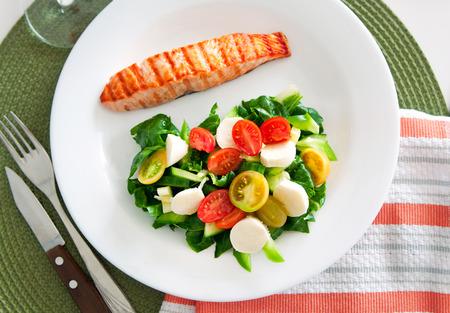 Leckere Scheibe gebratener Lachs, serviert mit Salat-Mix von Kohlblätter, Kirschtomaten und bocconcini Schnitt in Hälften, Gurken, serviert auf einem weißen Teller. Gesundes Essen. Selektiver Fokus, Draufsicht, Kopier-Raum Standard-Bild - 50923558