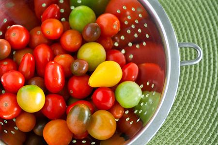 tomate: Colorful rouges tomates cerises jaunes et vertes lav�es dans une passoire inox, au rond-vert mat fond, copie espace Banque d'images