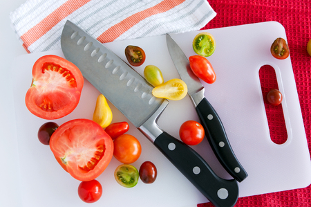 paring: Sharp and shiny chefs and paring knives lying on a cutting board with tomatoes of different size and color, several kitchen towels at background. Top view. Stock Photo