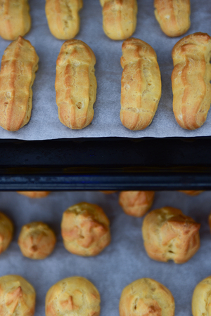 oven tray: Home made crispy oblong and round pastry eclairs on an oven tray, main focus on upper tray