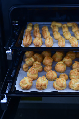 oven tray: Home made freshly baked crispy oblong and round pastry eclairs and profiteroles on oven tray, main focus on the front row of profiteroles at the bottom tray. Trays in black oven, copy space Stock Photo