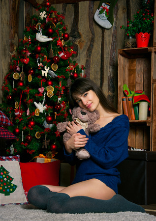 long stockings: Attractive brunette woman wearing knitted sweater and long stockings, sitting near decorated Christmas tee, enjoying her presents and playing with a toy. In interior on the floor