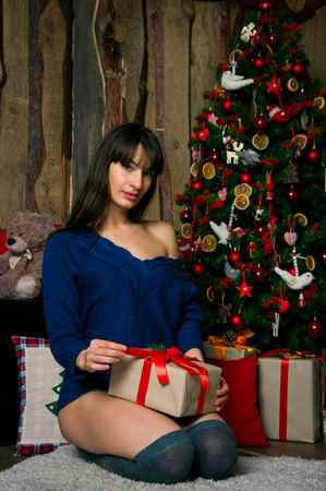 long stockings: Attractive brunette woman wearing knitted sweater and long stockings, sitting near decorated Christmas tee, enjoying her presents, opening a box with one of her wrapped gifts. In interior on the floor