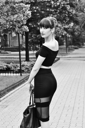 Black and white portrait of pretty young brunette woman model with beautiful butt wearing black top and long tight skirt, elegant high heels, holding her bag, walking down an alley, looking aside and enjoying the day.