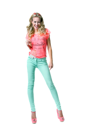 Pretty slim blond woman model with amazing long legs with round sunglasses on forhead, bright pink top, blue denim vest, turqouse pants, stylish platform shoes, sitting on the floor looking at camera photo