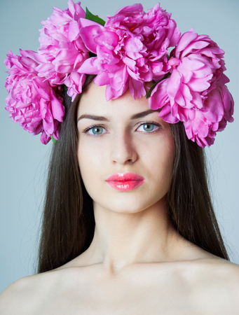 Beauty studio portrait of young pretty woman with natural makeup, bright pink lips, wearing flower wreath made of big peonies, looking at camera. Grey background