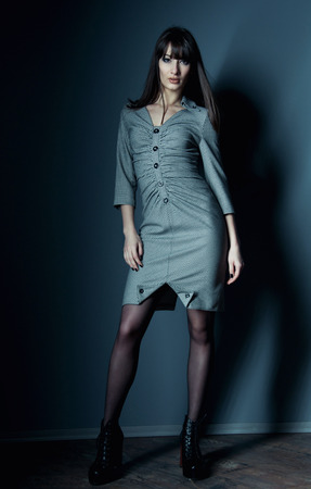 Pretty confident business woman with long straight hair wearing an elegant dress, standing, looking at camera. Over dark gray background in studio environment