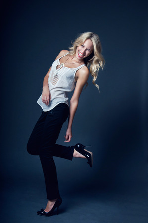 Happy laughing blond business woman wearing trousers and white shirt, having fun, dancing, jumping in studio over dark gray background photo