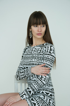 Portrait of beautiful brunette woman with long straight frindge wearing geometric earrings and black white dress, sitting on a chair and posing in studio. Natural makeup