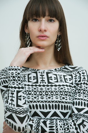 Portrait of beautiful brunette woman with long straight frindge wearing geometric earrings and black white dress and posing in studio. Natural makeup