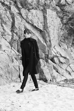 Beautiful brunette woman wearing slim jeans, turtleneck, coat and sunglasses, walking outdoors along the beach near rocks, copy space photo