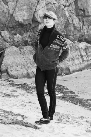 Black white portrait of elegant beautiful brunette woman model in boyish clothes like turtleneck sweater, knitted jacket, jeans, cap, atent leather shoes, walking outdoors on the beach near rocks photo