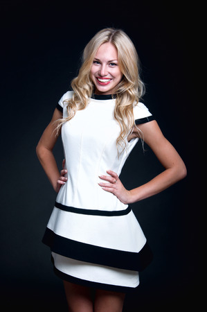 Beautiful young blonde woman wearing elegant black and white fashionable dress, posing in studio, smiling to the camera. Office work style clothing. photo