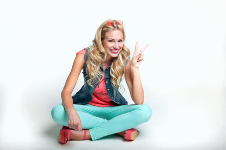 Happy beautiful blonde woman wearing slim jeans, vest, colorful top, pink sunglasses, sitting on the floor in studio, smiling with a toothy smile. White background, copy space photo