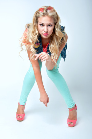 Beautiful blonde woman model wearing colorful clothes and posing in studio. White background. Blue jeans, vest, pink top, stylish shoes photo