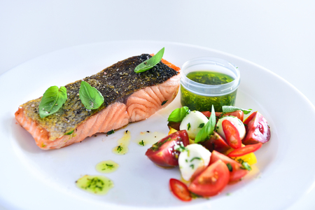 Delicious salmon steak with golden crispy skin served with basil leaves, fresh tomato and bocconcini cheese salad and herb infused oil Stock Photo