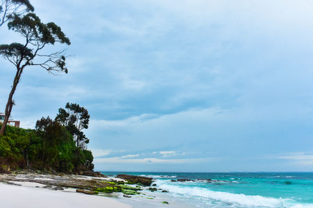 One of the most beautiful beaches in Australia with white sand on a moody rainy day, turquous water of the ocean, waves hit the shore Stock Photo
