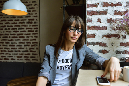 Beautiful brunette hipster business woman wearing a jacket and glasses, sitting in a cafe, looking at her phone, waiting for a call. Stylish grunge cafe 版權商用圖片