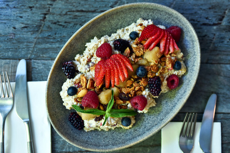 Breakfast idea: bircher muesli with honey granola, raspberries, sliced straberries, blueberries and blackberries, decorated with mint in a bowl on a wooden table