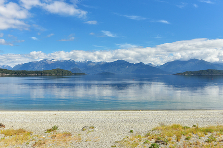 Blue clean waters of Manapouri lake with a beach with the view of Fiorland mountains in New Zealand 版權商用圖片