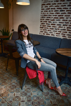 Portrait of a beautiful and confidenr brunette hipster business woman wearing a jacket and glasses, red nails manicure, tight jeans, sitting at the table in a cafe, looking at camera and smiling. Stylish grunge cafe